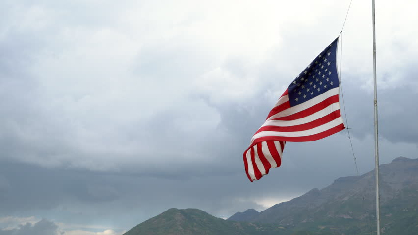 American Flag at half-mast blowing in the wind for death of a politician. | Shutterstock HD Video #1015489534