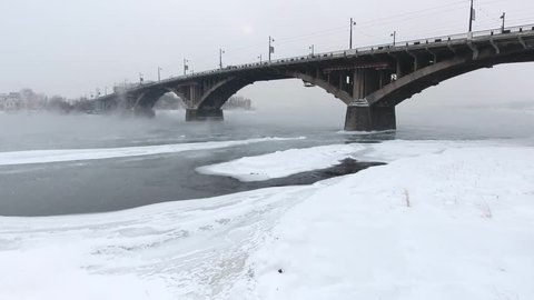 Aerial drone cinematic low approach to pillar. Dramatic flight above Angara river Irkutsk city. Center main arc bridge Extreme cold winter snow blizzard weather. Iceberg flow from Baikal