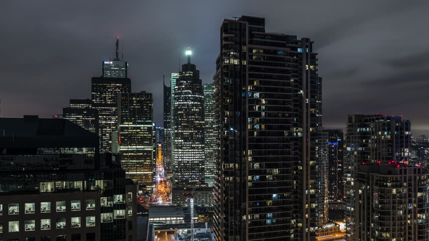 Huge epic wide city skyline views at night of the Toronto Canada downtown core. Office buildings, condominiums and urban modern architecture layer the skyline. Traffic drives down Bay street.   Shutterstock HD Video #1015570054