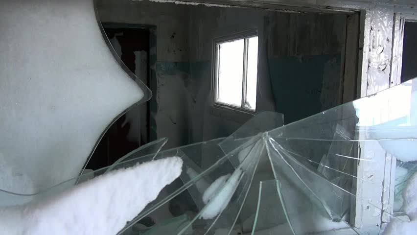 Broken windows in snow of abandoned house in ghost town of Gudym. Hopelessness in deserted city. Unique place for stalkers. | Shutterstock HD Video #1015572364