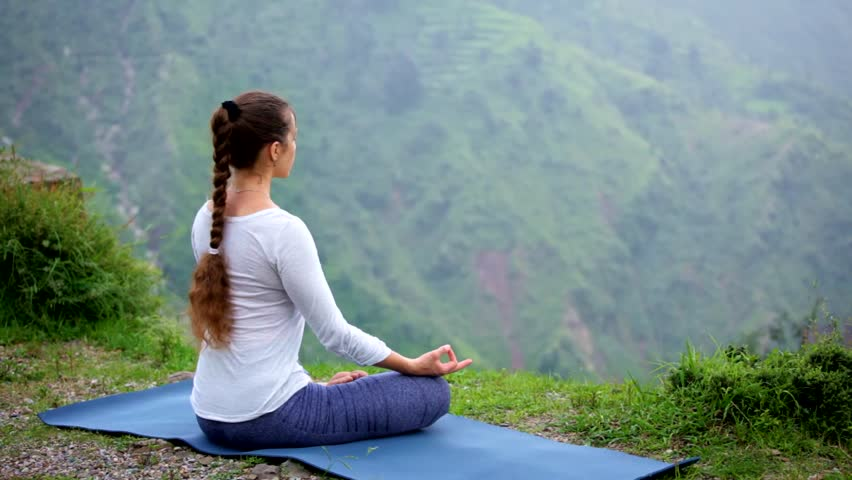 Woman doing yoga - meditating in Padmasana (Lotus Pose) outdoors in mountains on sunset | Shutterstock HD Video #1015584124