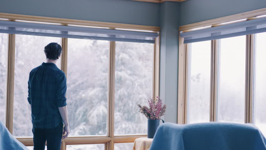 Young man walking to the window of his house and looking outside to the snowy trees. Shot with a RED camera. 4k footage.