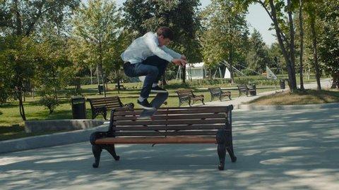 Skater doing ollie jump trick on over bench in skatepark, street skate trick gap slow motion