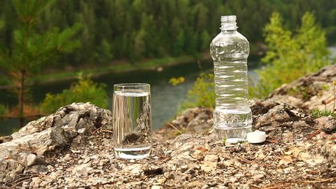 Man turn ON the appliance PH-meter in glass of water on mountain area. Theme of health and ecology. Slowmotion