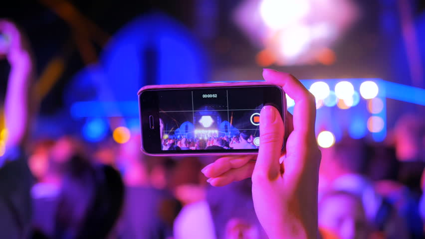 Unrecognizable woman hands silhouette taking photo or recording video of live music concert with smartphone at night. Photography, entertainment and technology concept