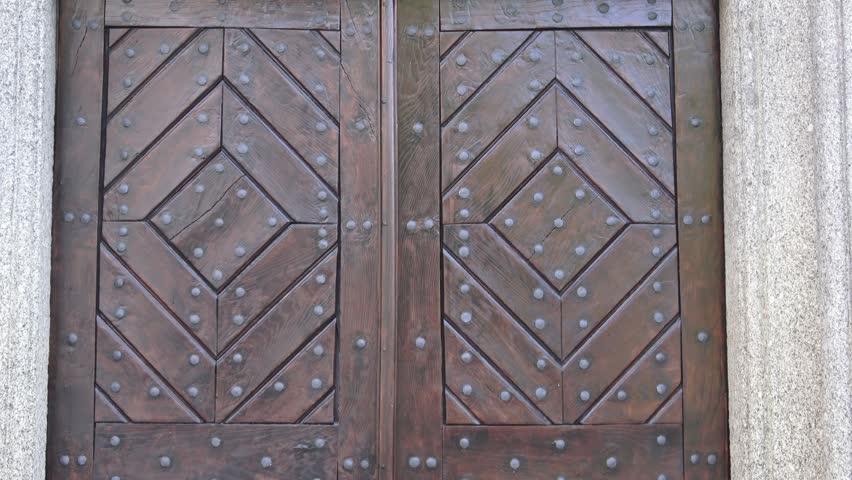 Old wooden entrance door. Wooden door with ancient patten. Ancient wooden door.