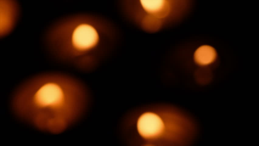 Blurred lit tealights against background