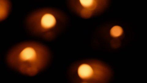 Blurred lit tealights against background