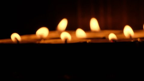 Lit candle tealights against dark background