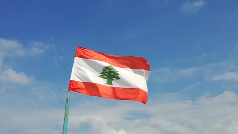 Lebanese National flag with emblem of Cedar waving in the wind in front of a blue cloudy sky