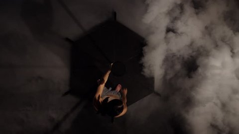 Girl dancing on a pole in the dark smoke studio. Black smoke background. Top view