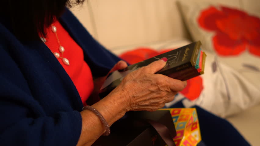 MONTREAL, CANADA - DECEMBER 24TH 2017: Grandmother Opening Christmas Gift During Christmas Eve #1015690654