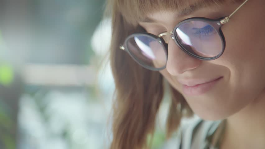The face of a beautiful brunette girl with glasses: she reads notes on a notepad and smiles. The morning of the modern girl: she looks at the diary, plans the day, enjoys. Lifestyle. | Shutterstock HD Video #1015703674