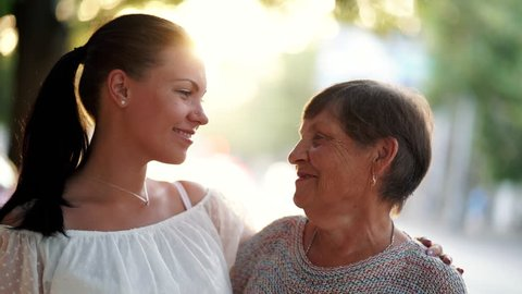 Beautiful portrait of grandmother and her granddaughter look at each other with love on summer street. Sun flares. Girl embracing granny with gratitude. Family concept. 4k