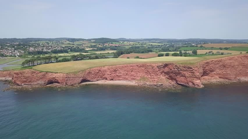4K aerial,ing toward red cliffs along the Jurassic Coast world heritage site