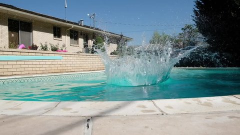 Young fit Caucasian man runs off diving board and jumps into a swimming pool in a backyard. Man in swimming trunks jumps into an outdoor swimming pool. Jumping into backyard pool making a splash.