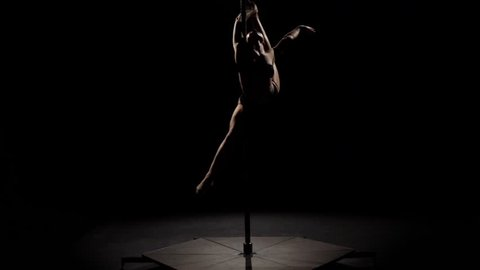 Sports tricks a sexy stripper in a dark studio. Black background. Slow motion. Silhouette