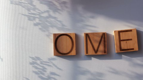 "The word ""HOME"" is laid out in wooden letters"