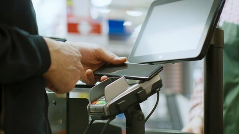 In the Supermarket Close-up Footage of the Man Paying with Smartphone at the Checkout Counter. Using Modern and Convenient Wireless NFC Paying System in Big Mall. Shot on RED EPIC-W 8K Helium Camera.