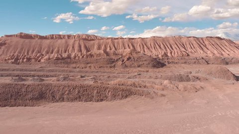 Cinematic aerial view of rocky sand mountain Atacama desert Chile. Drone rising up reviling mountains and snowy volcanoes in background far. Valle de la Luna.