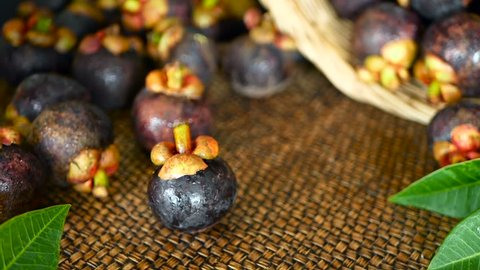 Top view selective focus Fresh delicious harvested mangosteens on wooden table. Thai Tropical Organic purple fruit in the basket. Exotic natural blurred background. Healthy food and eating concept.