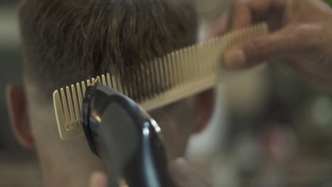 Hairdresser doing hair cut with hair machine and comb in barber shop. Hairdresser making hairstyle with electrical shaver in male salon. Close up hairdressing with trimmer and hairbrush