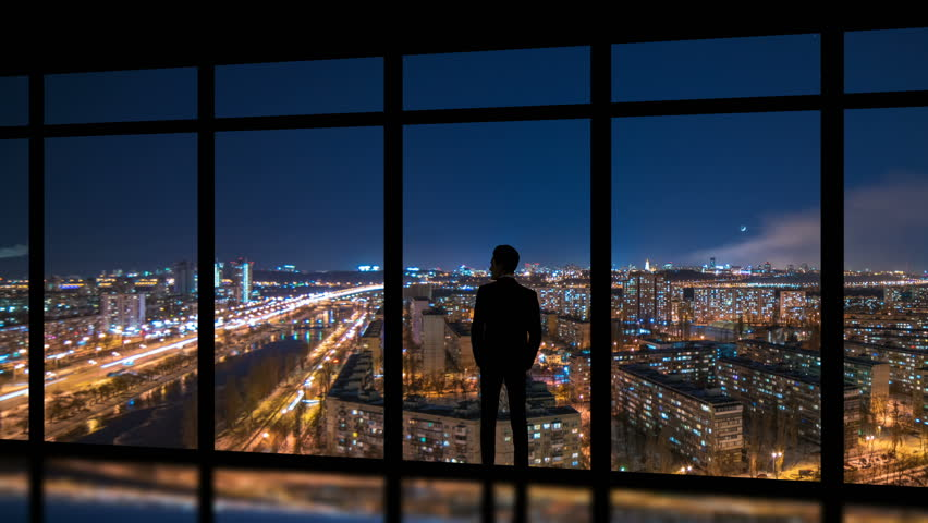 The man standing near windows on a night metropolis background. time lapse | Shutterstock HD Video #1015803394