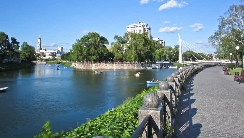 Pedestrian bridge across the river Kharkiv (The Maryinsky Bridge) and embankment timelapse, which is a favorite place of the city's lovers couples. Kharkov, Ukraine