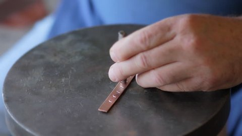 Crimean Tatar master makes a copper bracelet