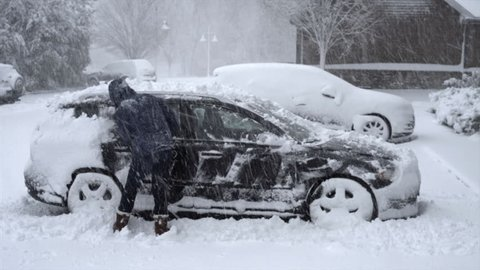 Man Shoveling Snow off Car During a Snow Storm