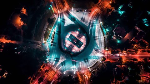 Aerial drone time lapse of a busy intersection at night moving traffic above city arch triumph Bucharest