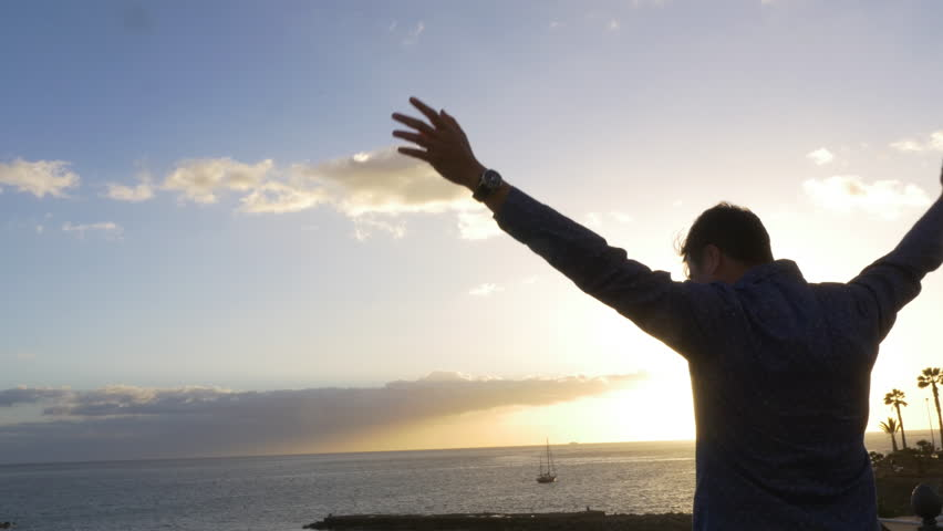 Man rises arms in joy in front of an ocean sunset panorama. Medium shot. #1015885384