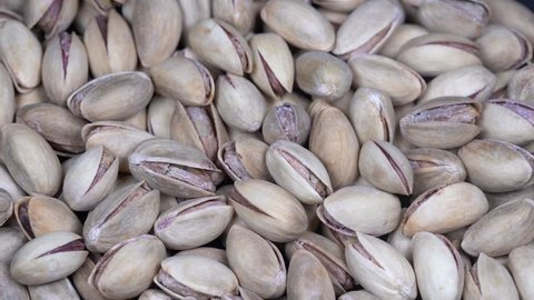 Dried roasted appetizing pistachios rotating, background salted pistachios, close up, macro