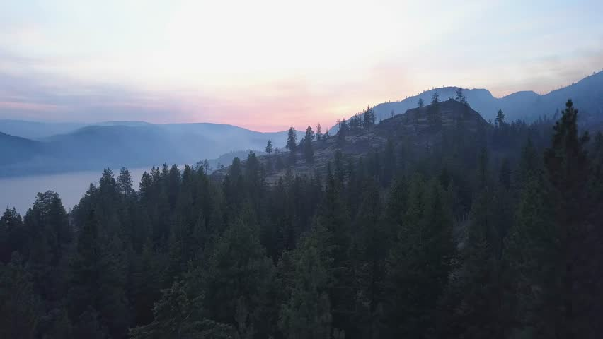 BC forest fire smoke covering mountains in 4k drone perspective. Rare view onto Okanagan landscapes affected by forest fire. Smoke covering trees, hills and lake. Sunset smoky skies