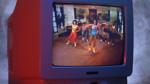 MONTREAL, CANADA - September 2018 : Group of people doing aerobic training on TV 80's style.Zooming out with fog giving a retro look at the scene.