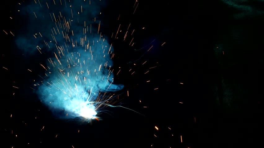Welder welds a metal part, a lot of sparks and smoke, close-up, welding, close-up, spark | Shutterstock HD Video #1015922164