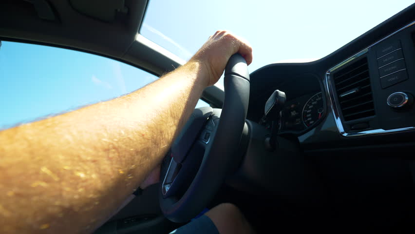 SLOW MOTION, CLOSE UP, LENS FLARE: Unrecognizable man handles the steering wheel of a modern car on a sunny summer day. Adult male commuting in his car. Hands controlling vehicle with black interior.