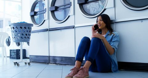 Happy woman talking on mobile phone at laundromat 4k