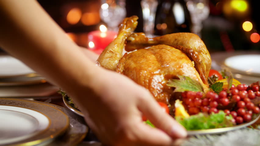 Closeup 4k video of young woman putting dish with baked chicken on dinner table served for Christmas
