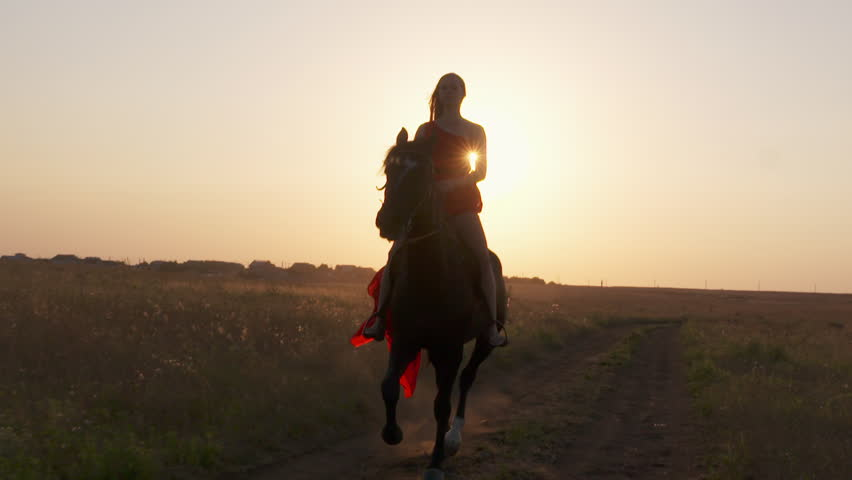 Young girl rider in red dress riding black horse against the sun in evening