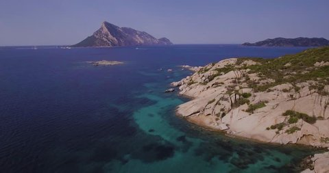 Aerial, Sardinia island and its rocky shore, beautiful emerald sea and Tavolara island on background