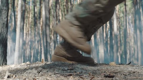 close shot as soldier's legs run through the forest