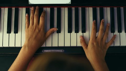 Female hands playing piano.Woman touches fingers on keys. Close up, high angle, camera from above