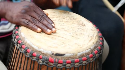 African Art. Men play handmade drums in an art market in West Africa.