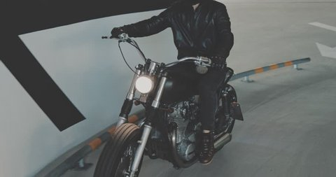 Motorbiker riding on a motorcycle in the parking lot in the city. Biker rides a vintage custom motorbike from 1970s in the garage. 4K video shooting by handheld gimbal