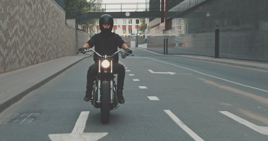 Motorcyclist drives on a motorcycle on the road in the city. Biker rides a vintage custom motorbike from 1970s . Urban lifestyle scene. Front view 4K video shooting by handheld gimbal
