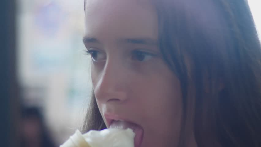 Girl teenager eating ice cream in a cone, outdoor. 4k, close-up.   Shutterstock HD Video #1016120284