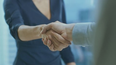 Out of Focus Businesswoman Shakes Her Hand with a Businessman. Hands in Focus. Finalizing the Deal and Concluding Contract with a Handshake. Shot on RED EPIC-W 8K Helium Cinema Camera.