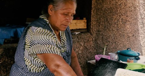 ZIRAHUEN, MEXICO - CIRCA MAY 2018 - Elderly senior Mexican woman rolling tortilla masa by hand and cooking them on a makeshift comal with a oil barrel lid over an open fire