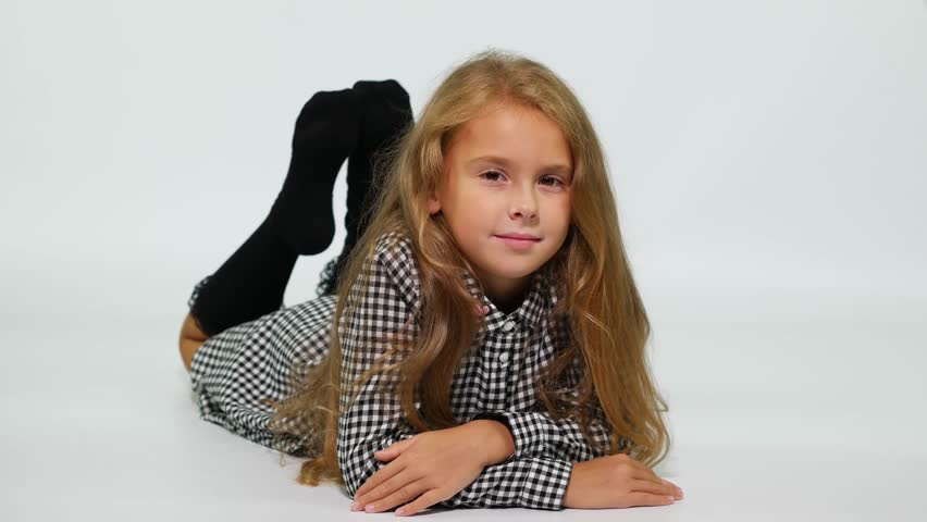 A girl in a checkered dress lies on the floor, gently smiling at the camera.  | Shutterstock HD Video #1016158054